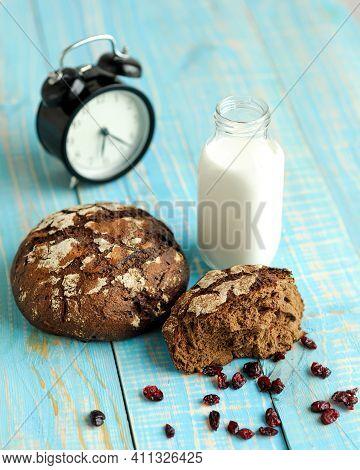 Dark Rye Bread Loaf With Crispy Crust, Glass Of Milk And Alarm Clock. Freshly Bakery Food In Working