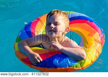 Playful Children In The Children's Pool, Happy Children Bathe With An Inflatable Circle.
