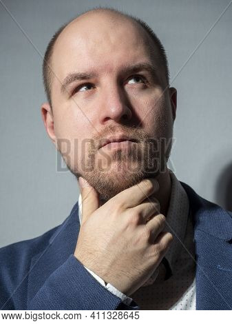 Portrait Of A Middle-aged Man In A Jacket And Shirt, Who Looks Up Thoughtfully. A Hand Holds His Bea