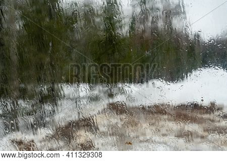 Wet Misted Glass With Dripping Rain Drops. View Of The Forest Through Misted Glass.