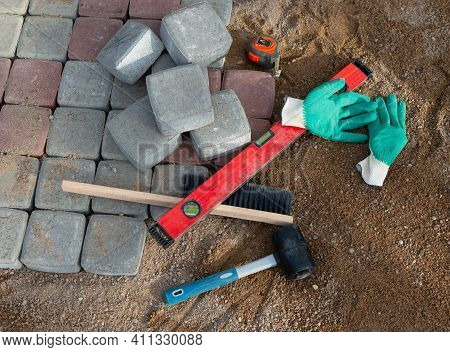Process Of Laying Paving Stones In Layers. Brick Pathway Paving Equipment Top View: Hammer, Level, B