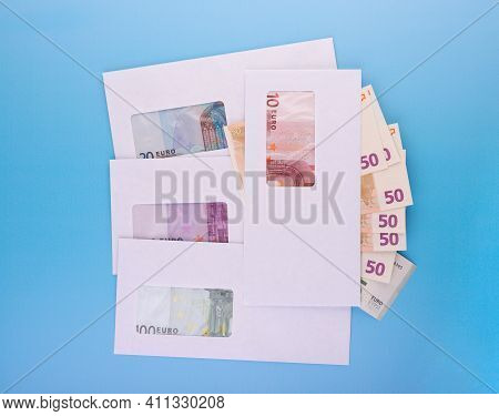 Stack Of Closed White Envelopes With Euro Bills Inside And Banknotes Beside Over Blue Background. Co