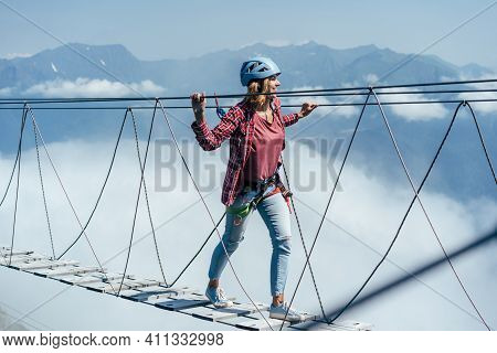 A Happy Woman Walks On A Suspension Bridge High In The Mountains At The Level Of A Cloud. Wanderlust