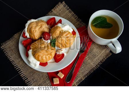 Mouthwatering Eclairs With Ice Cream, Whipped Cream And Fresh Strawberries With A Cup Of Green Tea,