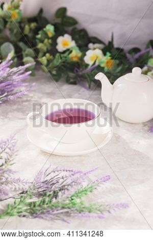 Purple Tea In A White Mug. On The White Table There Is A Mug And A Kettle, Lavender And Flowers On T