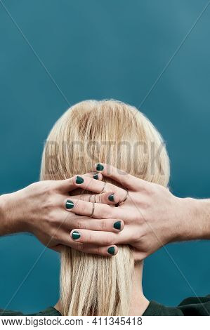 Rear View Of Young Caucasian Man With Long Blond Hair And Painted Nails While Posing On Blue Backgro