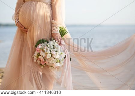 Beautiful Pregnant Woman With Flowers Holds Hands On Belly In Nature. Young Woman In Maternity Dress