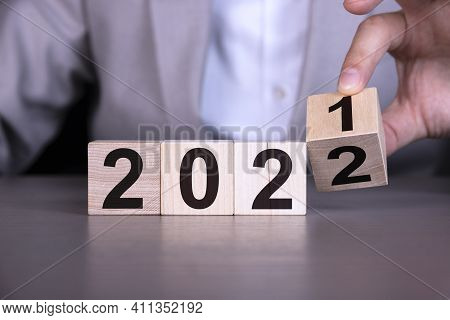 Businessman Flipping Wooden Cube Block To Change 2021 Year To 2022 Year , New Business Year Changing