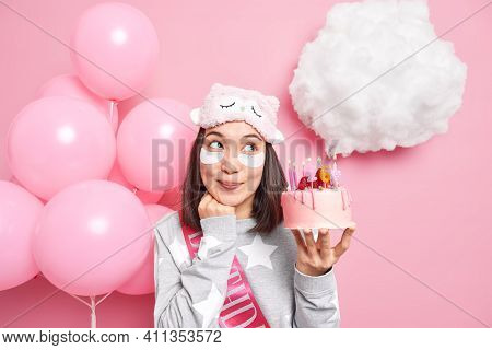 Photo Of Dreamy Asian Woman Looks Above Thinks About Wish Before Blowing Candles On Cake Celebrates