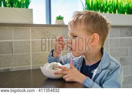 Cute Little Boy Enjoying Ice Cream In Cafe
