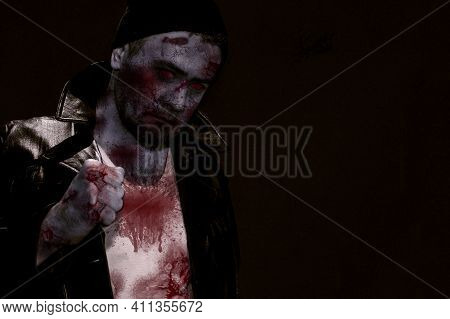 Horror Scene Of A Man With Bloody Face. Zombie In Jacket. Toned Image. Horror Concept