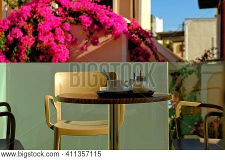 A Table With A Cup Of Coffee And Sugar On A Balcony In Sunny Santorini Greece