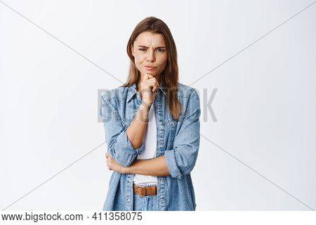 Girl Having Doubts. Woman Frowning And Staring At Camera Thoughtful, Hesitating About Deal, Standing