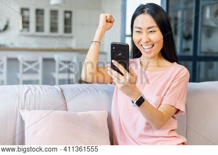 Overjoyed Asian Woman Holds A Smartphone Sitting On The Sofa At Home, Looks At The Screen And Celebr
