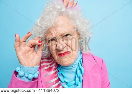 Headshot Of Displeased Grey Haired Mature Woman Looks With Grumpy Expression At Camera Keeps Hand On