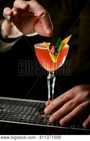 Close-up Of Mans Hands Decorating Glass With Alcoholic Cocktail By Beautiful Flower