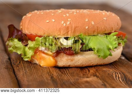 Tasty Hamburger On A Wooden Table, Close Up.