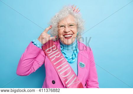 Awesome Happy Grey Haired Woman Makes Rock N Roll Gesture Enjoys Cool Birthday Party Dressed In Fest
