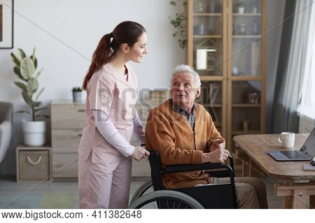 Portrait Of Senior Man In Wheelchair Looking At Caregiver Helping Him, Copy Space