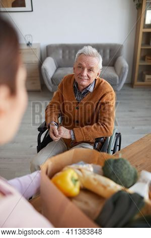 High Angle Portrait Of Smiling Senior Man In Wheelchair Looking At Female Nurse Bringing Groceries,