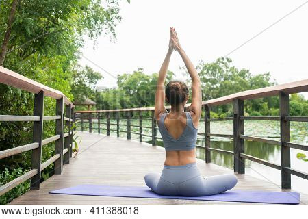 Portrait Of A Young Woman Doing Yoga In The Garden For A Workout. Concept Of Lifestyle Fitness And H