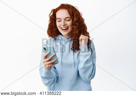 Image Of Happy And Satisfied Redhead Woman Rejoicing As Looking At Smartphone Screen, Achieve App Go