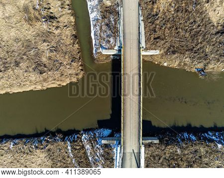 Small Bridge Over Dirty Olt River In Romania Aerial Drone View At Early Spring.