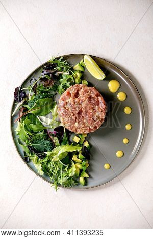 Tuna Tartare With Green Salad, Lime, Avocado And Mustard Sauce Serving On Ceramic Plate Over White T