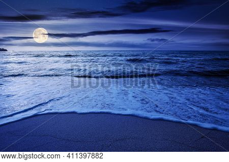 Summer Vacation At The Seaside At Night. Beautiful Seascape In Full Moon Light. Calm Waves Wash The