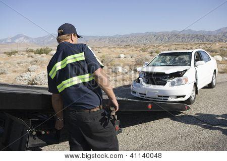 Man towing damaged car away poster