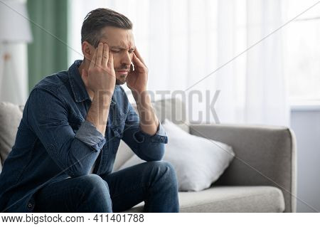 Stressed Middle-aged Bearded Man Having Headache, Sitting On Sofa At Home And Rubbing His Temples, C