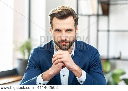 Successful Masculine Businessman In Formal Expensive Suit, With Neat Stubble, Sit, Holding Hands In
