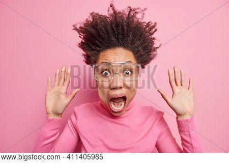 Studio Shot Of Stupefied Emotional Crazy Woman Raises Palms Keeps Jaw Dropped Stares Terrified Screa