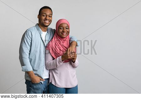 Family Photo Of Cheerful Loving African American Young Muslim Couple Hugging On Grey Studio Backgrou