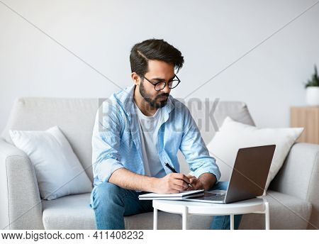 Online Education. Young Eastern Man Study With Laptop At Home And Taking Notes, Millennial Arab Guy