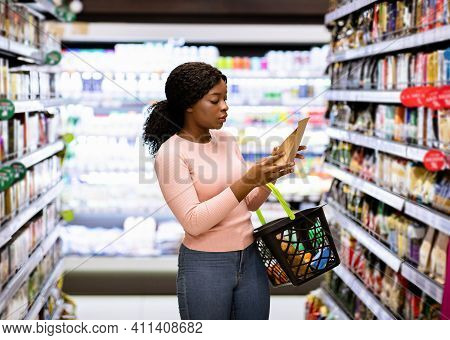 Beautiful African American Woman Making Choice Of Products At Supermarket. Focused Female Consumer S