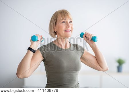 Home Workout. Happy Senior Woman Doing Domestic Training, Exercising With Dumbbells, Strengthening H