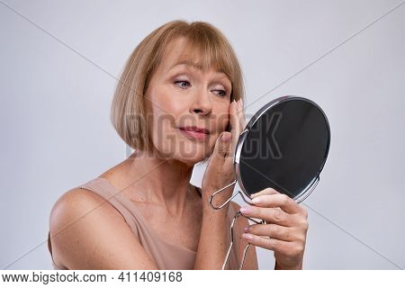 Portrait Of Beautiful Senior Woman Looking In Miror, Checking Her Wrinkles Over Light Studio Backgro