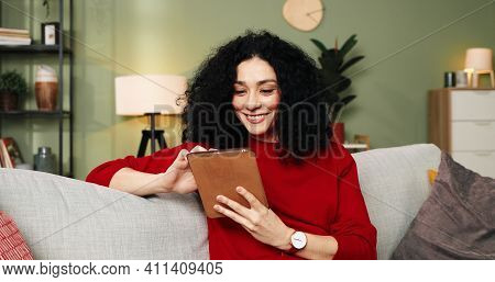 Portrait Of Happy Cheerful Young Caucasian Pretty Female With Curly Hair Sitting On Sofa In Cozy Roo