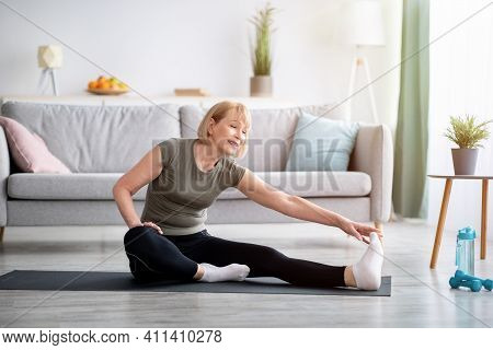 Home Workout. Sporty Senior Lady Stretching Her Leg On Yoga Mat In Living Room, Copy Space. Positive