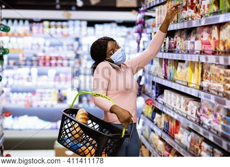 Black Female Customer In Mask Calling On Mobile Phone While Shopping For Food, Reaching Upper Shelf