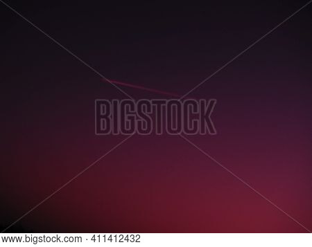 The Plane And The Trail In The Sky Of A Crimson-borj Color. Abstract Background On Space Or Aero The