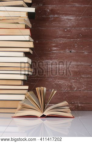 Science And Education -  Open Book On A Group Pile Books And Wooden Background. With Reflection