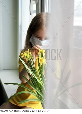 Little Girl In Medical Mask Sitting On The Windowsill With Yellow Daffodil Flowers. Covid 2021. The