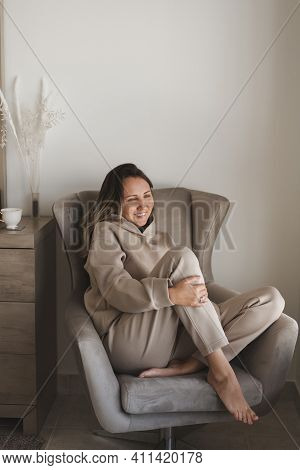 Happy And Positive Woman With A Smile On Her Face Sitting In A Cozy Armchair At Home. Loungewear Fas