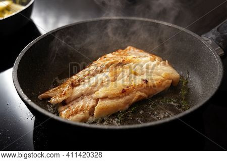 Cod Fish Fillet Sautéed With Thyme In A Steaming Frying Pan On The Black Stove, Copy Space, Selected