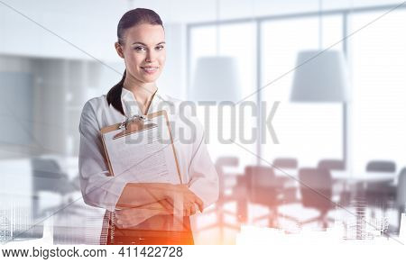 Office Woman In White Shirt On Background Of Business Conference Room, Holding Business Files. Conce