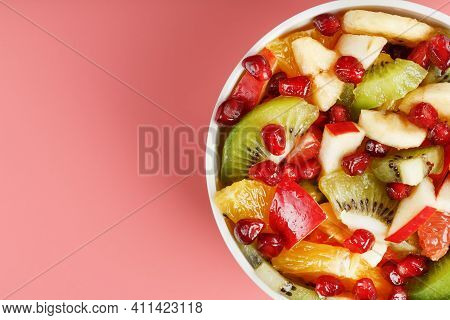 Bowl With Fruit Salad On A Pink Background. Juicy And Ripe Fruit Slices.