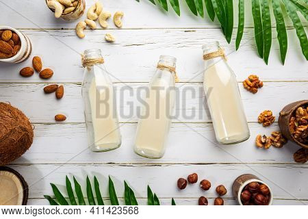 Vegan Non Dairy Nut Milk In Bottles And Various Nuts On White Wooden Background. Lactose Free Milk S
