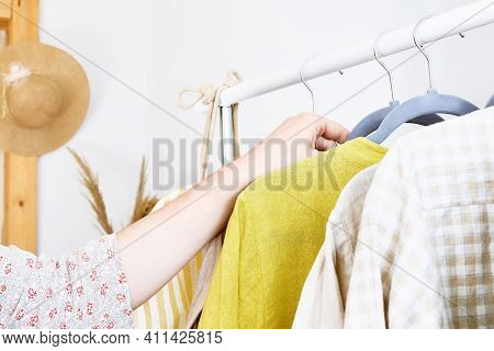 Woman Takes Linen Dress On Hanger From Clothes Rack. Slow Fashion. Conscious Consumption. Crisis In